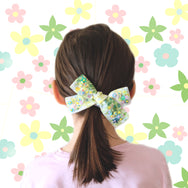 Girl with bow ponytail and flower background.
