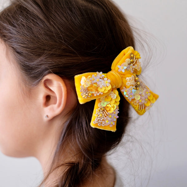 Model with yellow velvet hair bow embroidered with sequin.