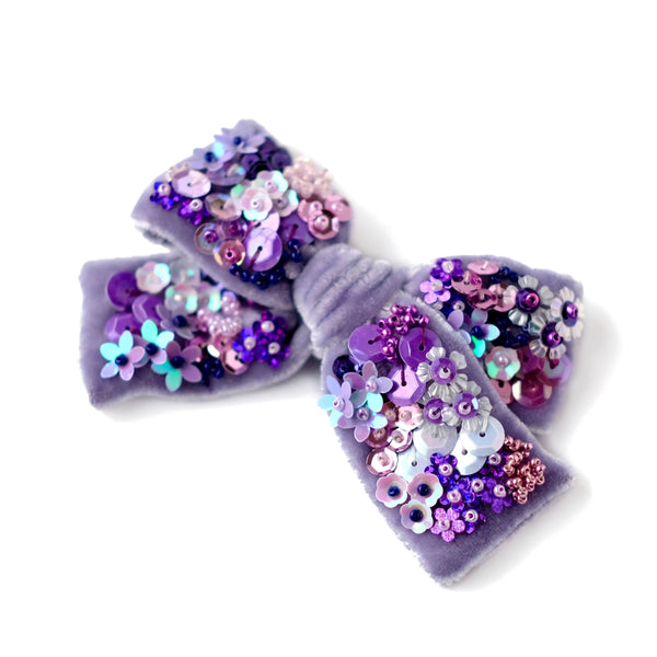 Velvet hair bow with sequin in lavender color.