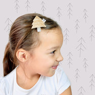 Model wearing a gold pine tree hair clip.