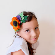 model with orange felt flower headband