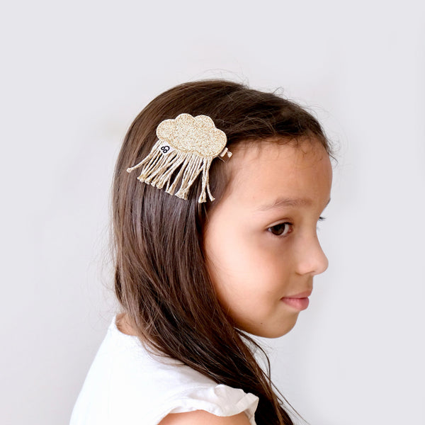 Model with rain cloud hair clip in gold.