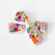 White velvet bow embroidered with colorful sequin.