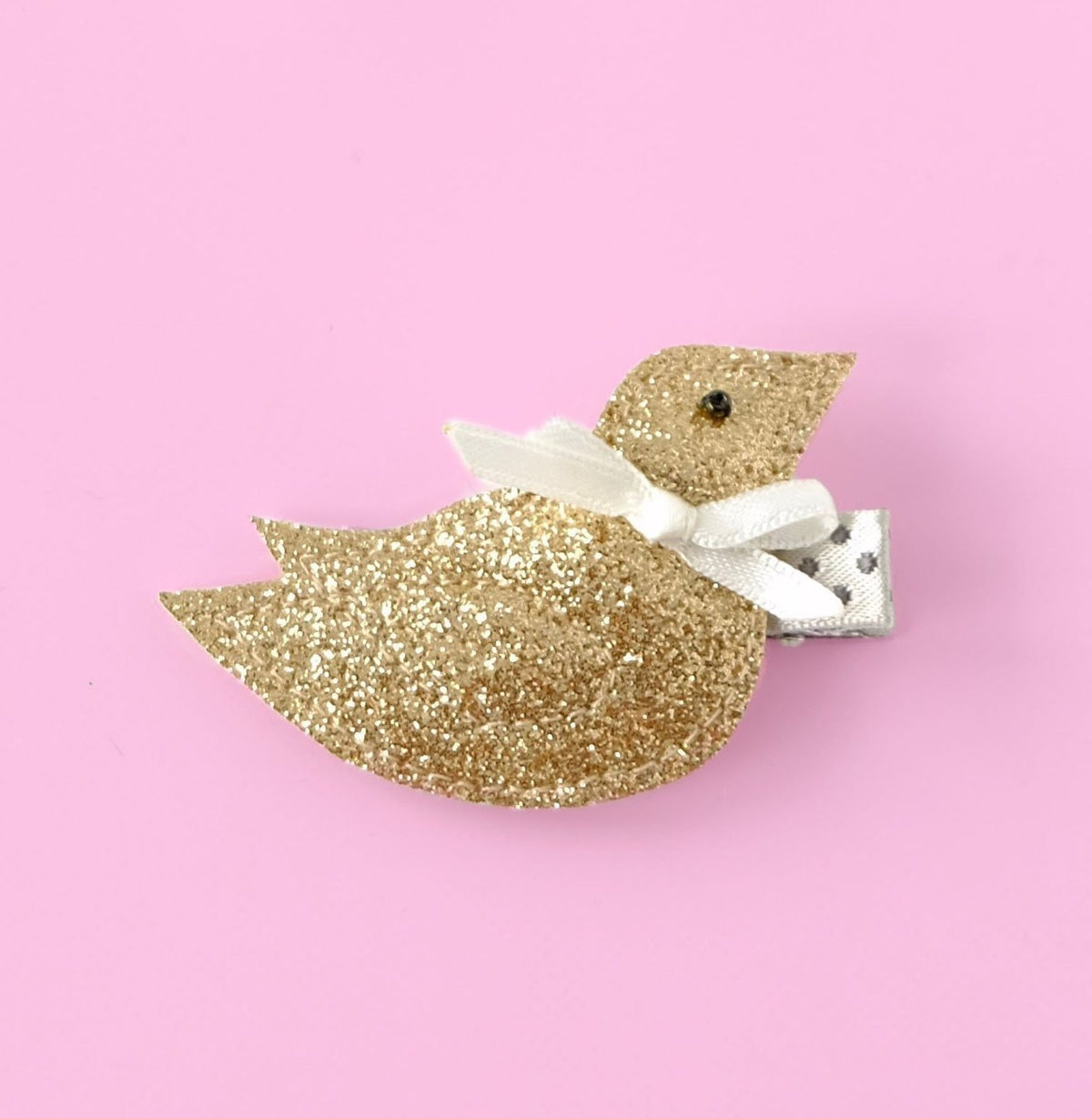 small bird hair clip in gold on pink background