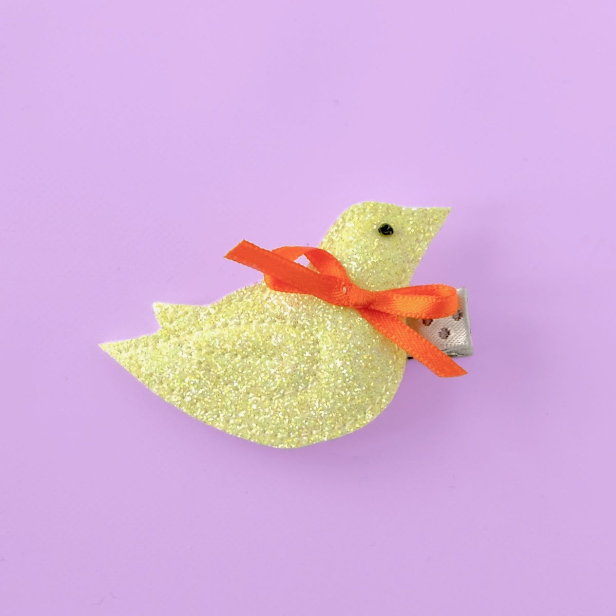 small bird hair clip in yellow on purple background