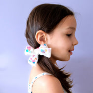 Model with white velvet bow with pink and blue sequin embellishment.