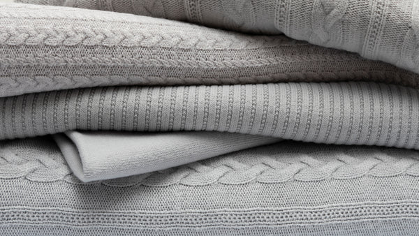Gray knitwear pieces with different textures folded on top of each other