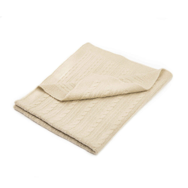 Beige Grete Knitwear baby blanket with a cable-knit design folded over a white background