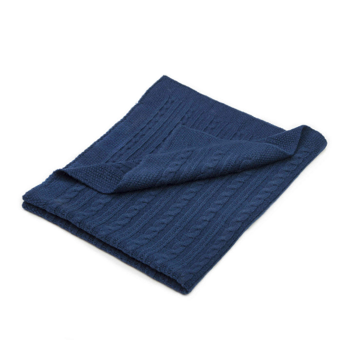 Blue Grete Knitwear baby blanket with a cable-knit design folded over a white background