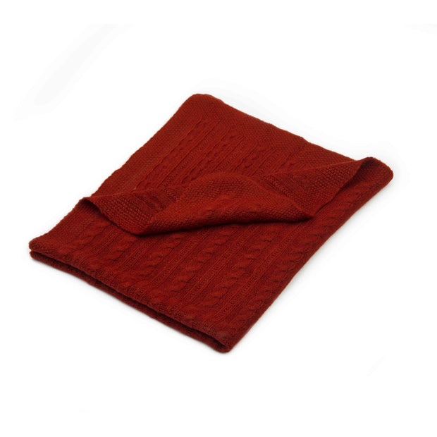 Folded red baby blanket on white background with a cable-knit design