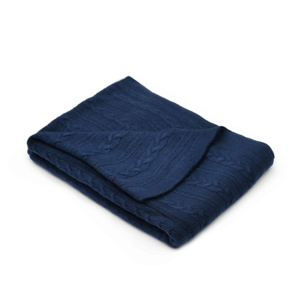 Blue throw blanket with a cable knit design folded over a white background for Grete Knitwear brand