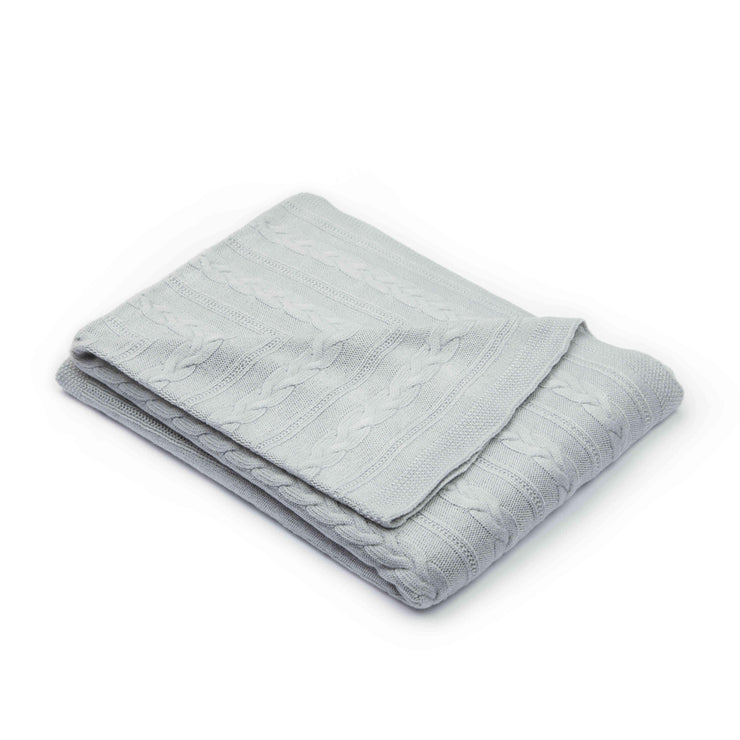 Gray throw blanket with a cable knit design folded over a white background for Grete Knitwear brand