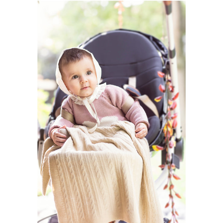 baby girl sitting in her carriage cover with Cable-Knit Baby Travel Blanket Grete