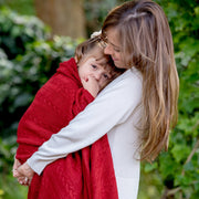 mom holding her toddler wrapped in grete throw in red