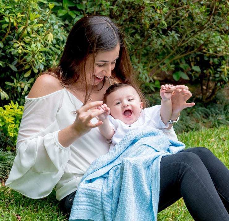 mom laughing with her baby cover with Grete Baby Cable-Knit Swaddle Blanket