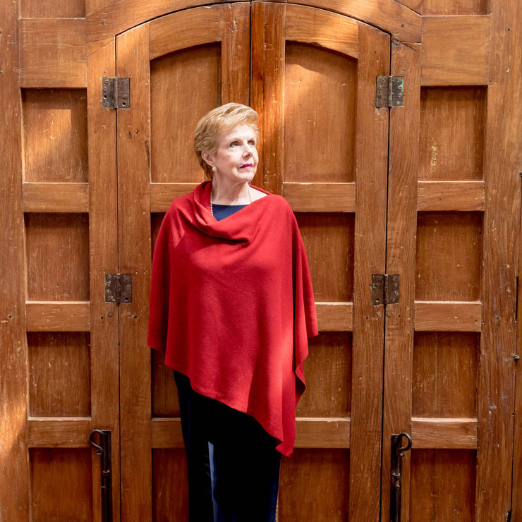 lady wearing red poncho wrap by grete in front of wooden door