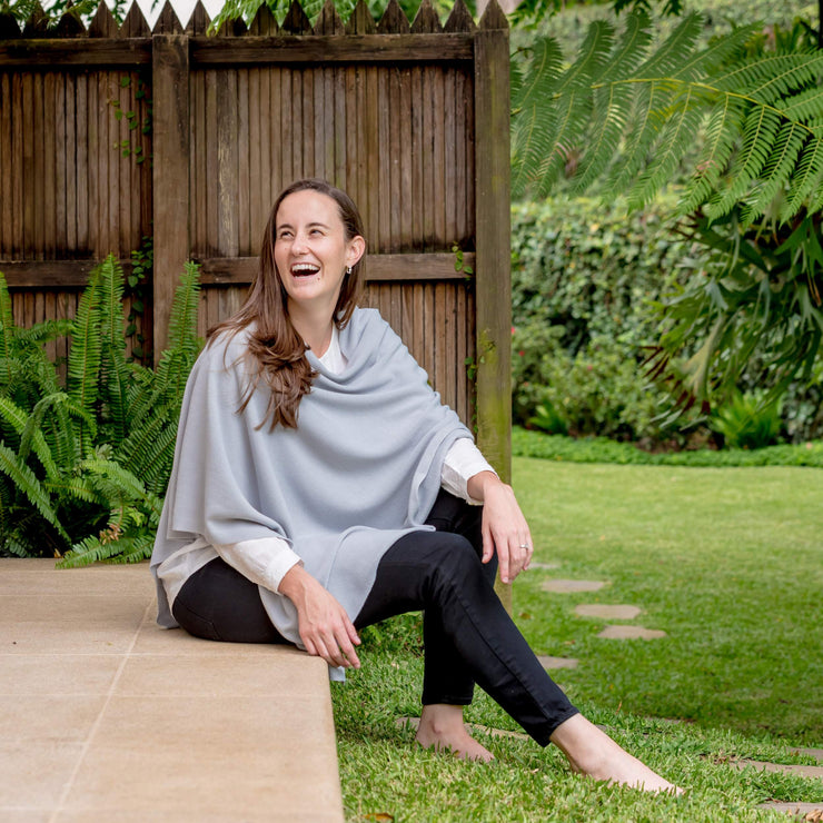 model sitting in the floor wearing grey poncho wrap by grete