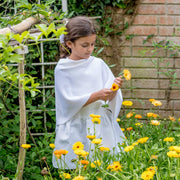 girl picking yellow flowers wearing white poncho of grete