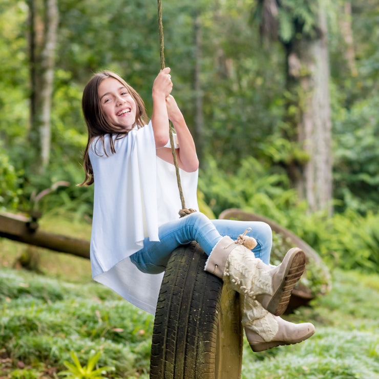 girl swinging herself over tire wearing white poncho grete