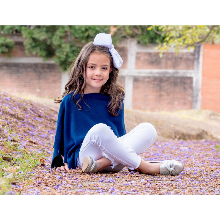 girl sitting in the ground wearing white jeans and grete blue poncho