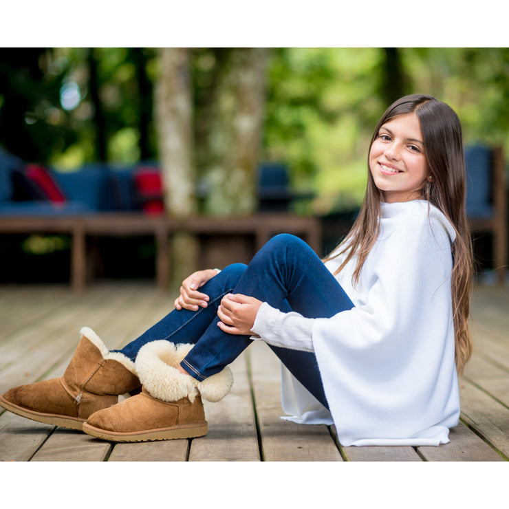 teen sitting on the floor wearing jeans and white poncho wrap by grete