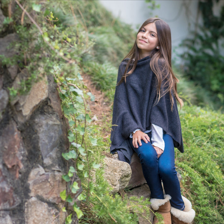 girl sitting in rocks wearing oxford poncho wrap by grete