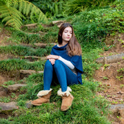 teen sitting in the grass wearing jeans and blue poncho wrap by grete