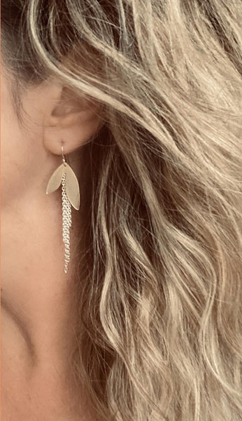 close up ear and neck photo of fair skinned model with blonde highlighted beach wave long hair wearing an earring with two large gold leaves and long silver chains dangling down from between the two leaves