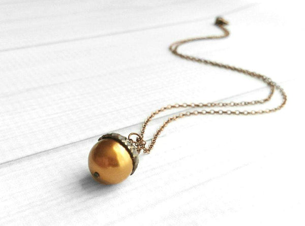 Copper Acorn Necklace laying on white background, rust brown shiny Swarovski pearl pendant in antique finish on thin delicate aged rustic chain
