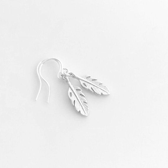 Silver Feather Earrings - tiny detailed plumes in a soft matte silver finish dangle from small simple delicate silver plated shiny ear hooks