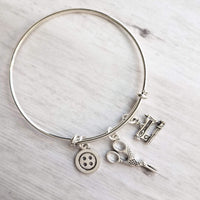 Sewing Charm Bracelet - seamstress hobby/tailor gift - silver adjustable bangle double loop wire w/ tiny sewing machine, scissors, button - Constant Baubling