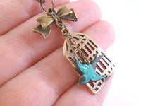 Birdcage Necklace - antique brass bird cage pendant / little bronze bow - free flying small aqua sparrow - oval link chain - Escape Flight