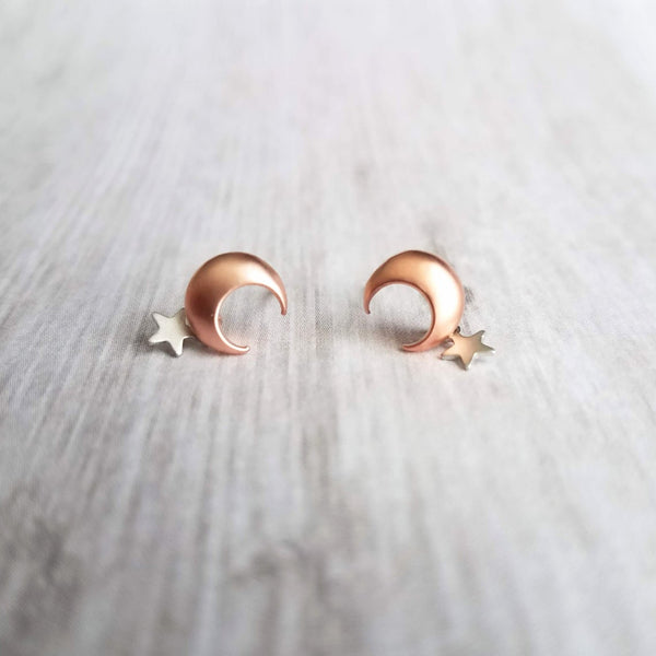 small matte finish pink rose gold crescent moon stud earrings with tiny silver rhodium single star that dangles below the moon, wood grain grey background