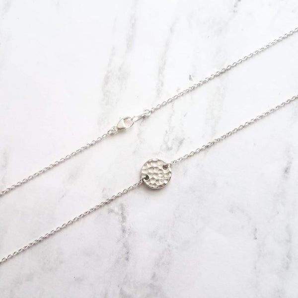 small 1/2 inch silver hammered round disc pendant on delicate thin silver chain with lobster clasp; shown laid out on a white marbled surface