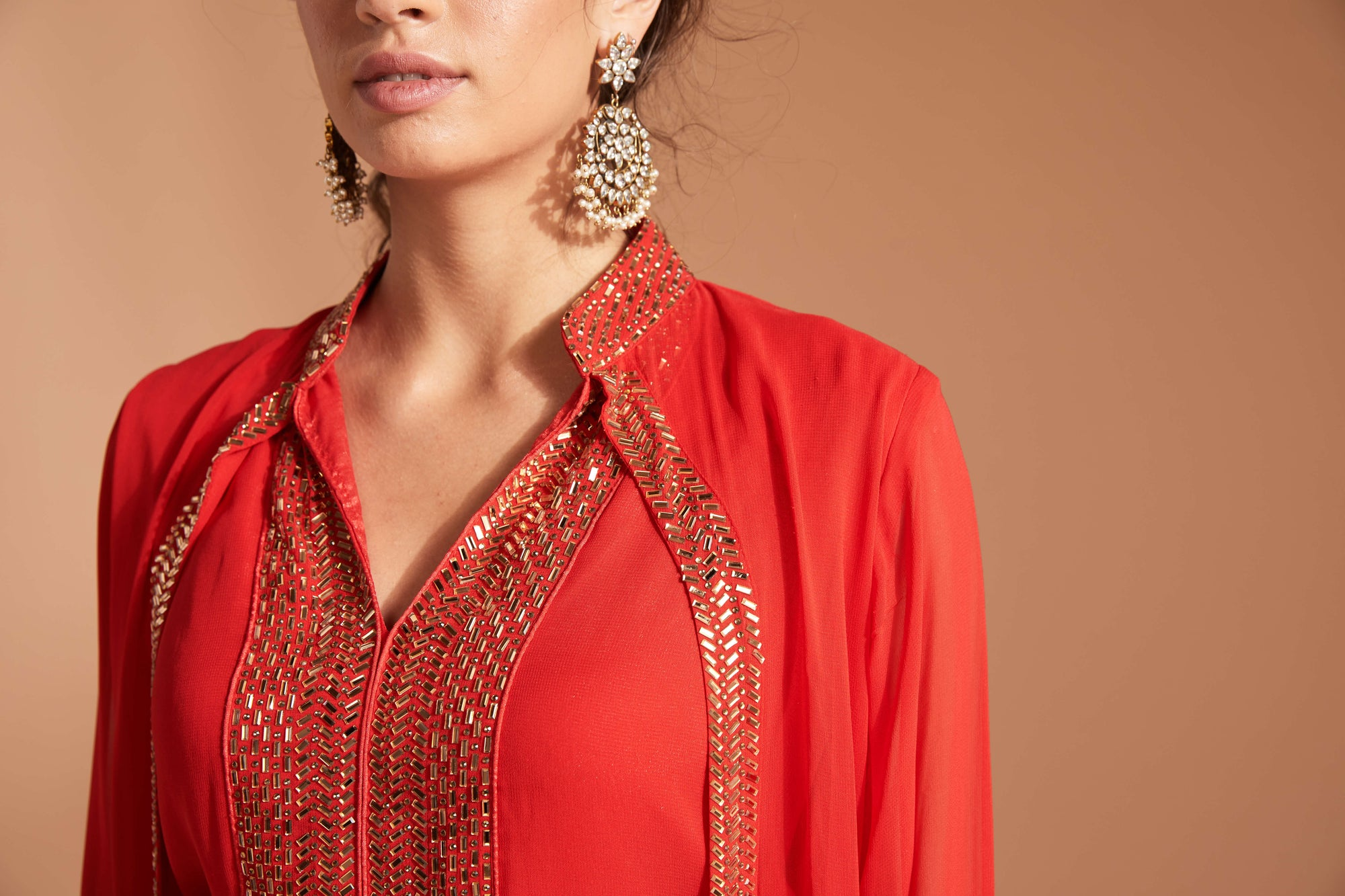 Red outfit with sequin work paired with beautiful Indian jewel earring