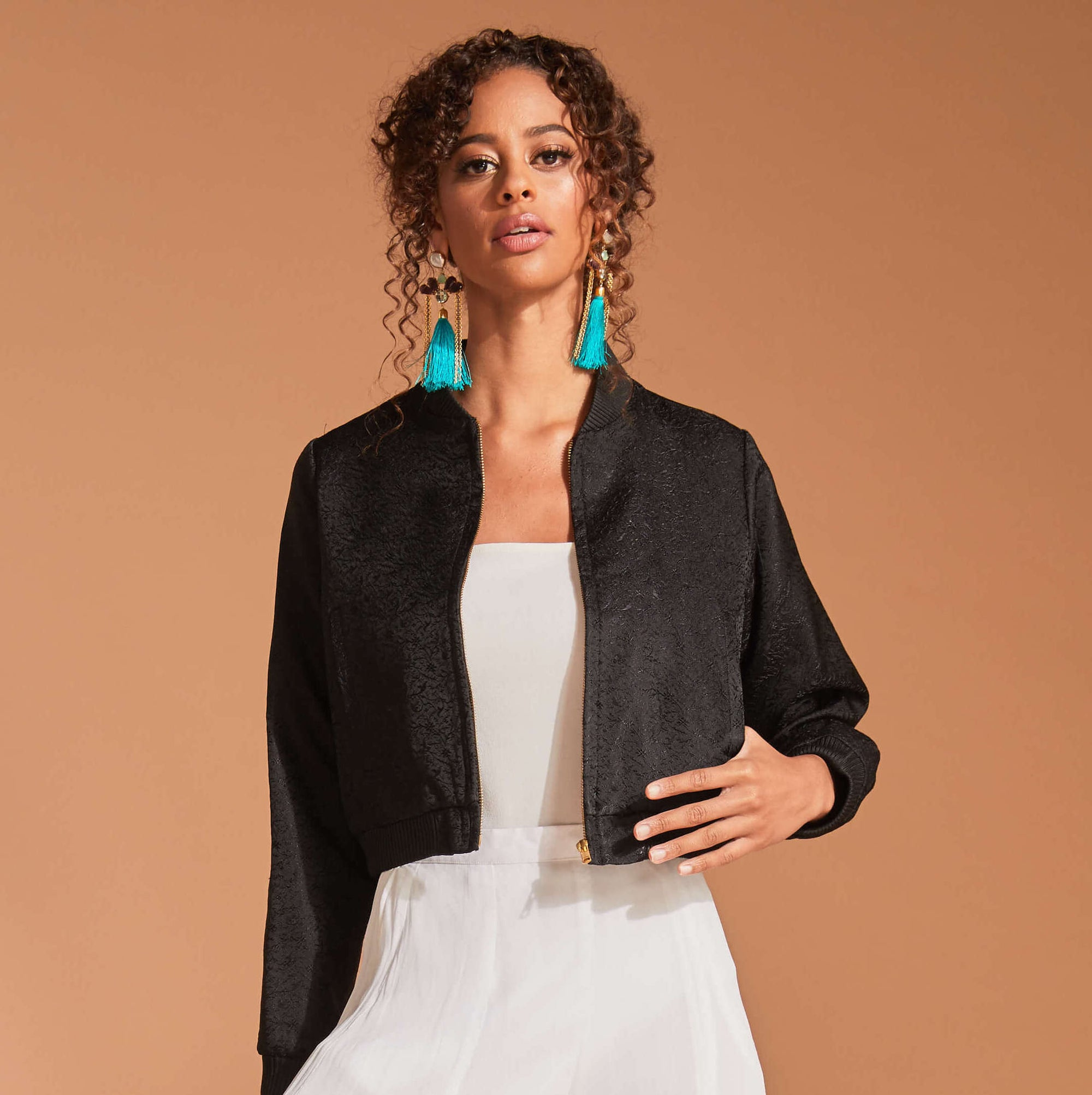 Black bomber jacket with turquoise earrings