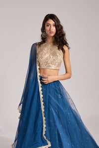 Lehenga with blue sequin skirt and nude halter-style mirror work blouse, with tulle underlayer