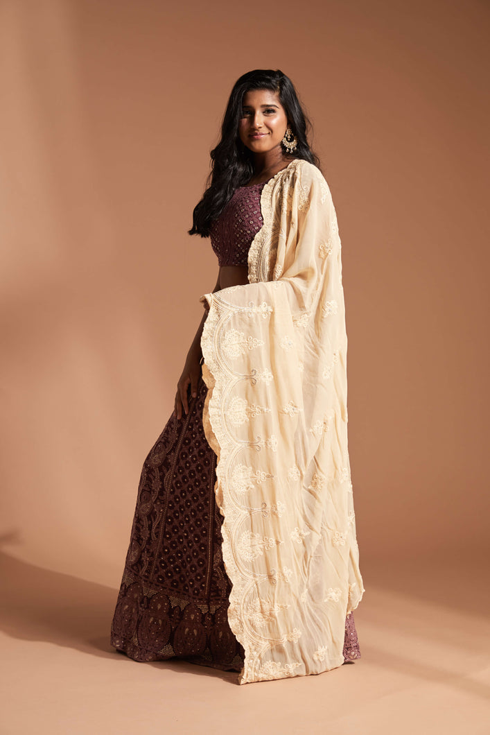 Burgundy lehenga made with lucknowi/chikankari work and featuring a cap sleeve blouse and cream scallop dupatta
