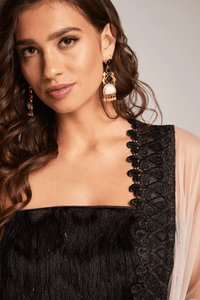 Model wearing black tassel top with black and gold earrings