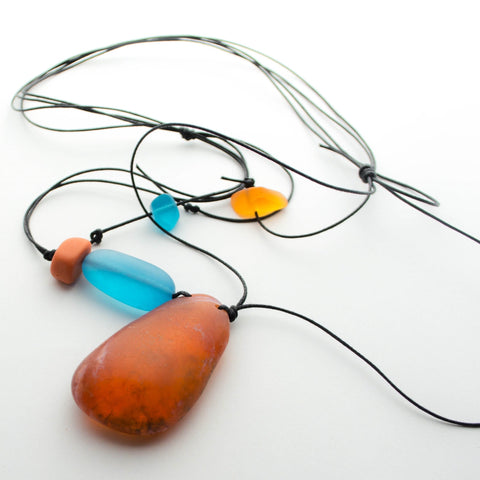 Orange resin pendant with adjustable cord.