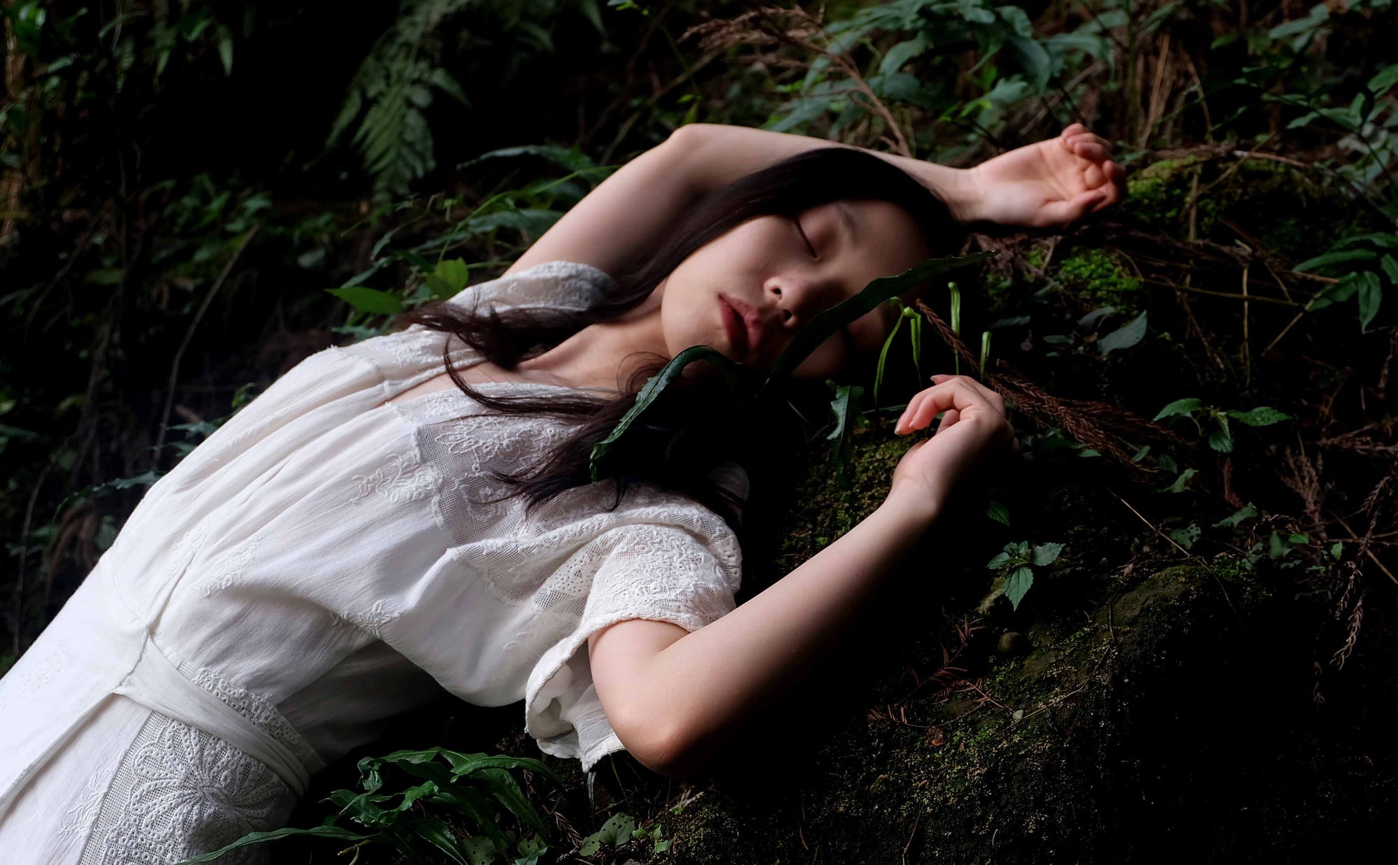 girl in white laying in forest