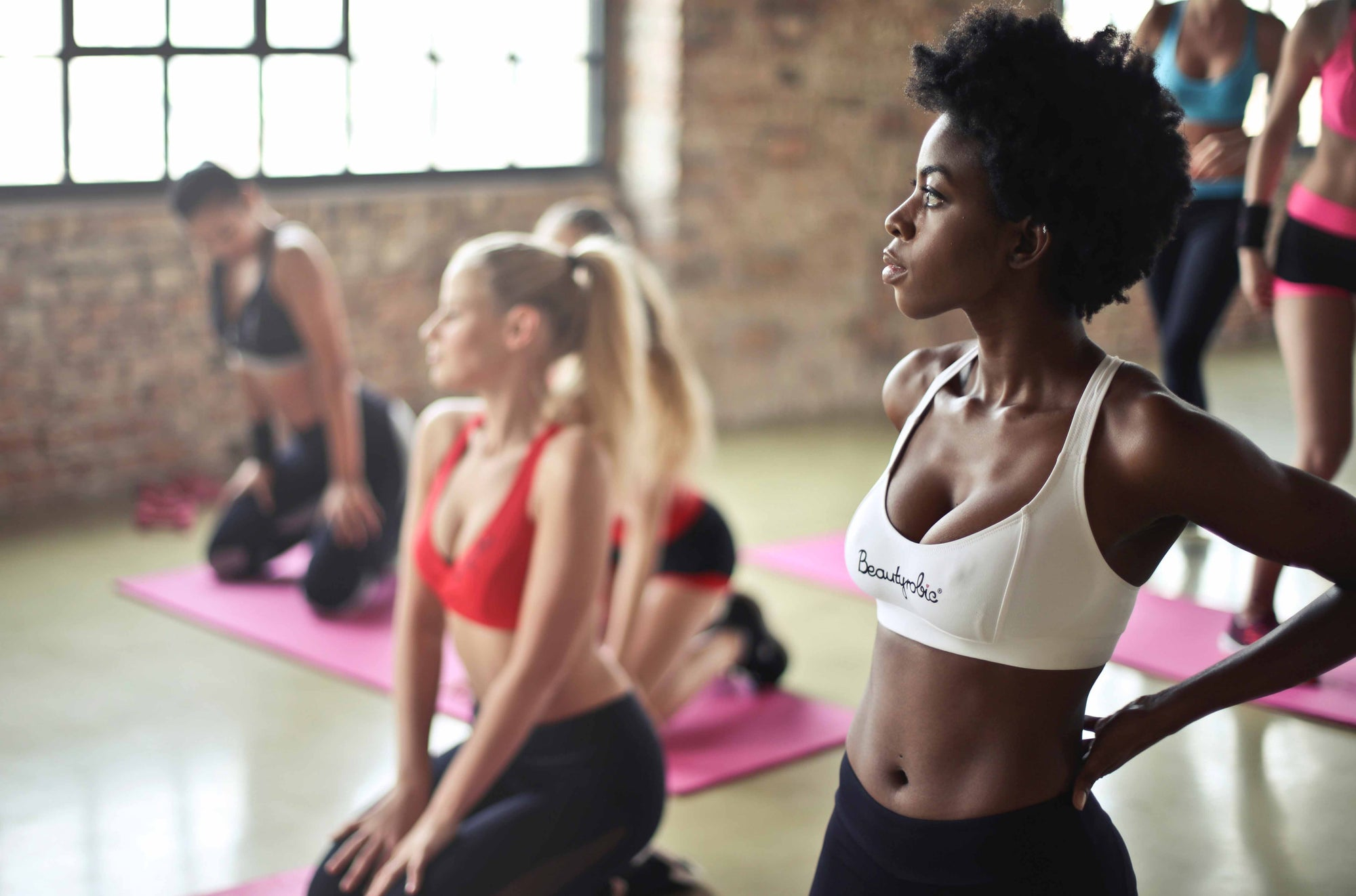 Women in a gym class sitting on yoga mats