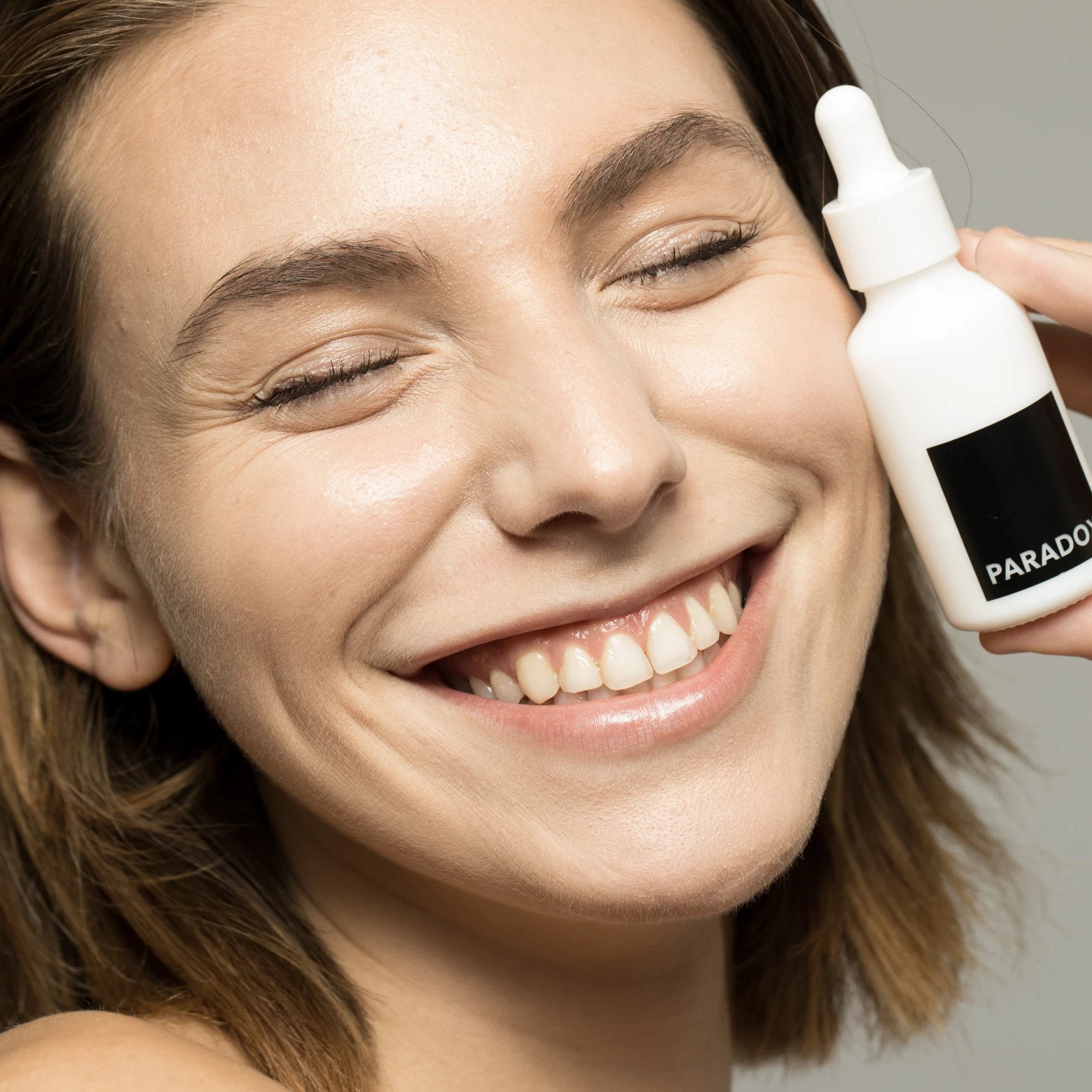 Model smiling while holding Paradox Beauty's Vitamin C Serum