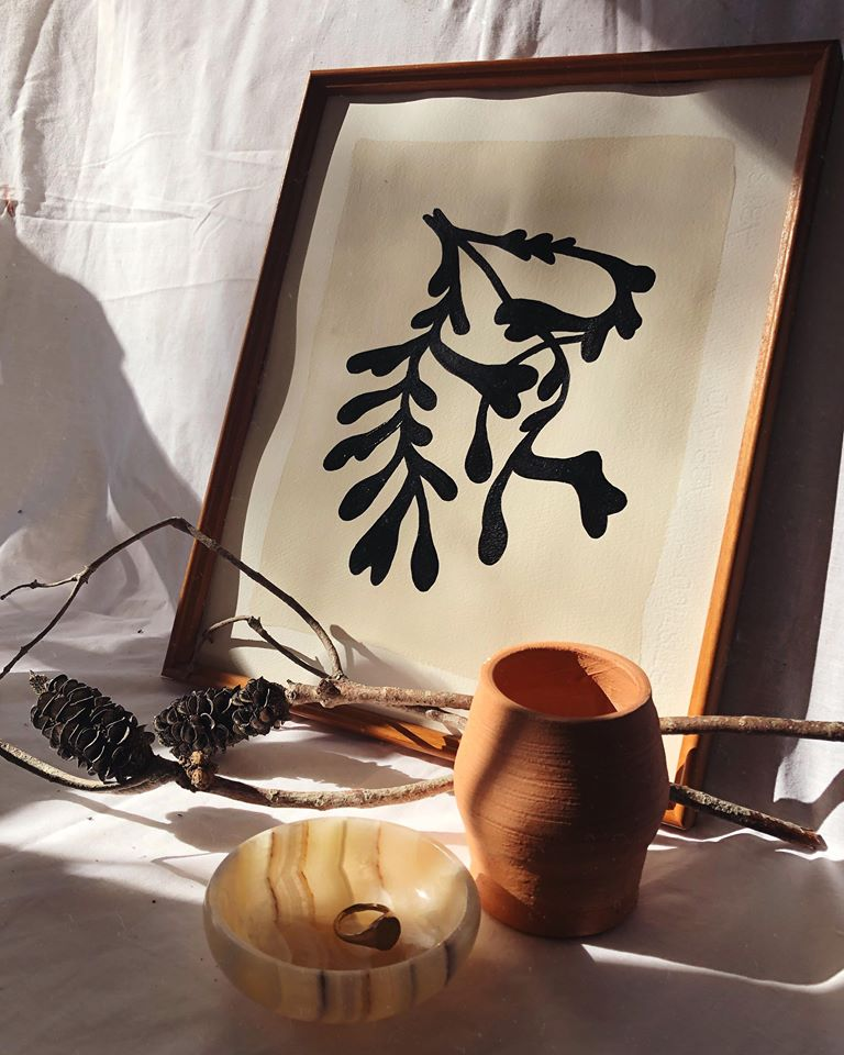 Still life photograph of a painting, a terracotta vase and some trinkets
