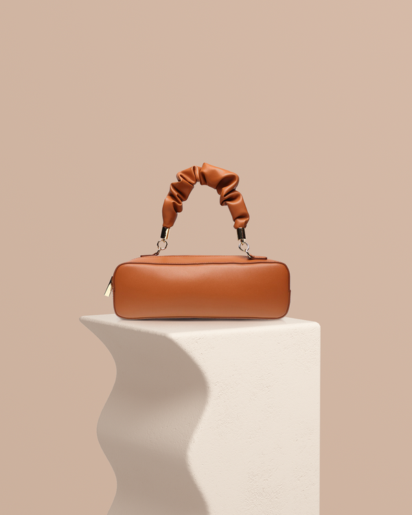 Hazel camel leather handbag front view on pedestal
