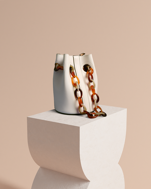 Scarlett leather bucket bag in latte with acrylic straps front view on pedestal