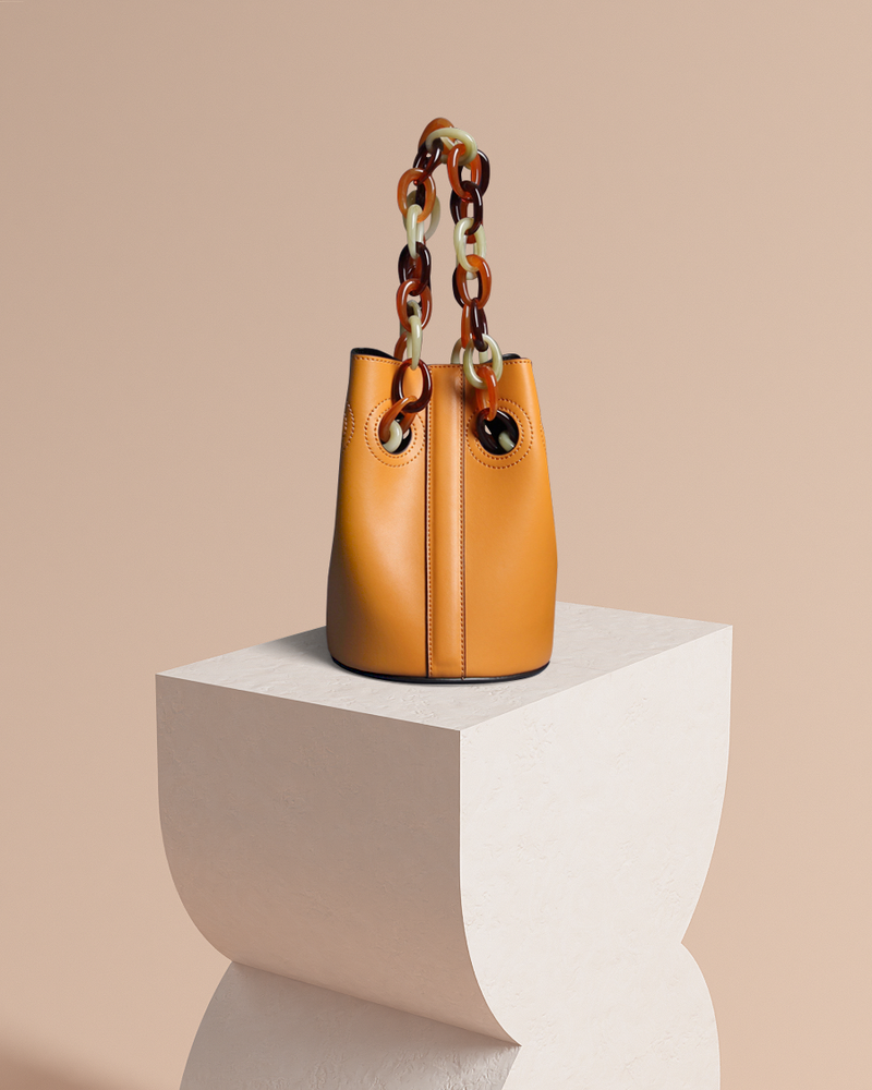 Scarlett leather bucket bag in camel with acrylic straps up front view on pedestal