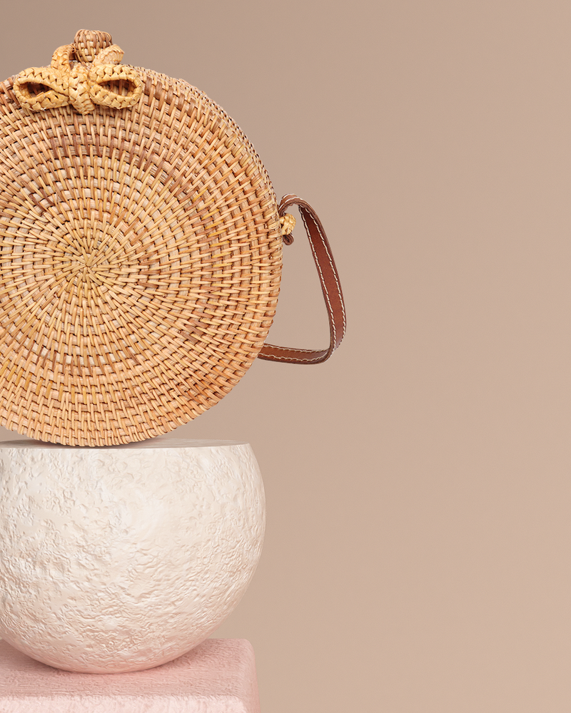 Bali natural rattan and straw bag on pedestal side detail view