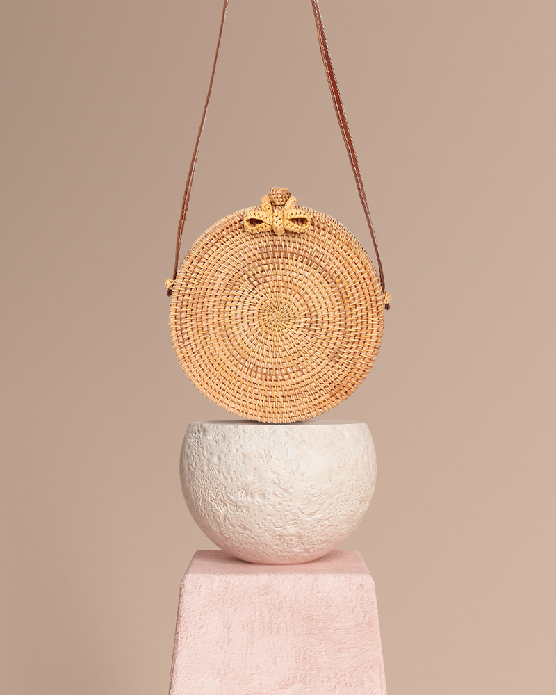 Bali natural rattan and straw bag on pedestal front view
