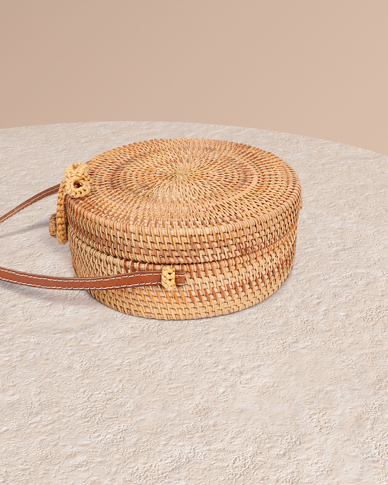 Bali natural rattan and straw bag on pedestal side view and leather shoulder strap